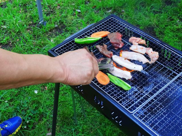 トングでコンロのバーベキューと野菜の焼き加減をチェック